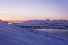 Sunset behind the snowy mountains in Norway. Sunset behind the snowy mountains in Tromso, north of Norway Stock Image
