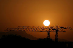 Sunset behind steel cranes. Sunset background behind a pair of steel metal cranes in Egypt Royalty Free Stock Photography