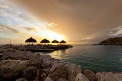 Sunset behind straw cabanas at tropical bay Stock Images