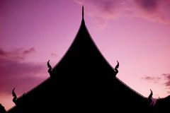 Sunset behind a temple in Chiang Mai, Thailand. Sunset from behind a temple in Chiang Mai, Thailand. The temple is dark and is a silhouette Stock Photo