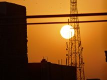 Sunset behind tower at evening. Beautiful sunset behind cables can be used for backgrounds or projects related to enviornment stock image