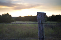 Sunset behind wire fence and post stock photo