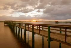 Sunset behind a wooden pier over water royalty free stock photos