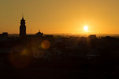 Sunset on bell. The silhouette of the city rooftops and church bell tower Stock Photos