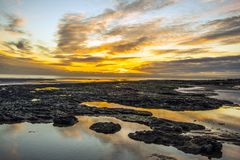 Sunset on Bexhill beach in East Sussex, England. The rock pools at low tide reflect the setting sun at Bexhill in East Sussex, England stock photo