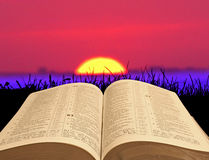 Sunset bible. Photo of open holy bible set against a golden sunset scene with red sky area ideal for own text etc Royalty Free Stock Photography