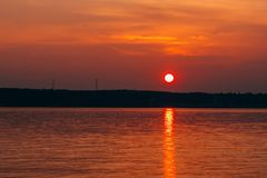 Sunset with big red sun over the water of sea. Sunset with big red sun over the water of the sea and the silhouette of the shore Royalty Free Stock Images