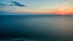 Sunset from a bird`s flight. Over a calm sea Royalty Free Stock Images