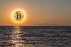 Sunset with bitcoin symbol. Concept of cryptocurrency falling royalty free stock photography