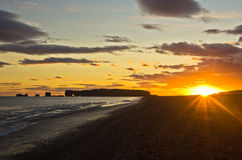 Sunset on black beach with Dyrholaey rock in background,Iceland Stock Photo