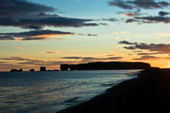 Sunset on black beach near Vik with Dyrholaey rock at background Royalty Free Stock Photography