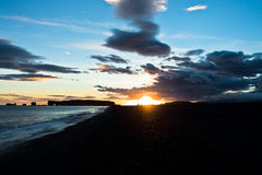 Sunset on black beach near Vik with Dyrholaey rock at background Stock Images