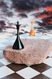 Sunset. Black and white chess queen on a background of sunset sky Stock Photography