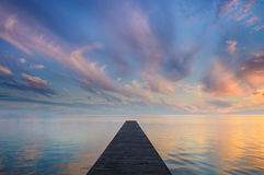 Sunset in Blue & Orange. Tranquil symmetric shot of a jetty leading into a lake. Accompanied by an awesome sunset spectacle Royalty Free Stock Photo