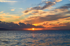Sunset on the blue sea with clouds. The sun between clouds. Royalty Free Stock Photos