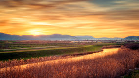 Sunset and blurred clouds illuminate the fertile fields Stock Image