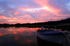 Sunset boat. Beautiful sunset colors reflects on the calm sea, preparing a little boat for his sleep Stock Photography