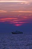 Sunset boat. Boat at sunset sailing under sun Stock Image
