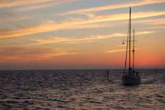 Sunset with boat. A sailing ketch returns after an afternoons sail Stock Photo