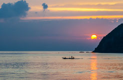 Sunset and boat with fisher on the island. Koh Phangan, Thailand Royalty Free Stock Photo