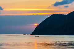 Sunset and boat with fisher on the island Royalty Free Stock Photography