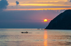 Sunset and boat with fisher on the island Stock Photo