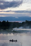 Sunset, boat and smoke. A photo of sunset at cloudy and dark weather. Bonfires are smoking on the small isle in the middle of the lake and people are rowing in a Royalty Free Stock Photography