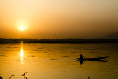 Sunset Boatman. A boatman in the Dal lake as the sun sets Royalty Free Stock Image