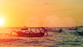 Sunset with boats in the foreground, Nusa Penida, Indonesia Stock Photo