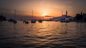 Sunset with boats and the old town of Rovinj in Croatia. Wonderful sunset in the awesome little town rovinj in istria - croatia. Golden hour is the right word Stock Photos