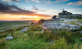 Sunset on Bodmin Moor. The silhouette of a lonely figure enjoying the sunset on top of a tor on Bodmin Moor in Cornwall Stock Photo