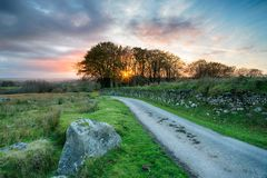Sunset on Bodmin Moor. Sunset over a country lane winding through Bodmin Moor in the Cornish countryside Royalty Free Stock Image