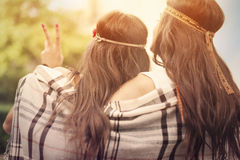 Sunset. Boho female friends with blanket looking on sunset Stock Photo