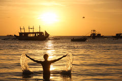 Sunset in Boracay. Silhouette of man on the beach splashing water with arms wide open and sailboats on the background at sunset in Boracay White Beach Stock Photo