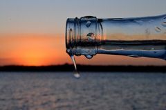 Sunset and a bottle 2. A picture of a sunset through the tip of a wine bottle in Mozambique. Only the tip is in focus but the droplets give it a bit of interest Royalty Free Stock Photo