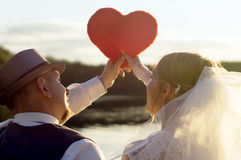 Sunset, the bride and bridegroom holding heart Stock Photos