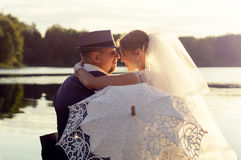 Sunset, the bride with the groom on the background of water Royalty Free Stock Images