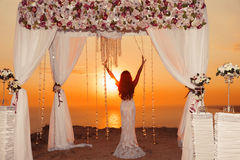 Sunset. bride silhouette. Wedding ceremony arch with flower arra Stock Photography