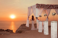 Sunset. bride silhouette. Wedding ceremony arch with flower arra Royalty Free Stock Images