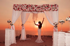 Sunset. Bride silhouette. Wedding ceremony arch with flower arra Stock Photos