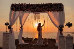 Sunset. bride silhouette. Wedding ceremony arch with flower arra Royalty Free Stock Photo