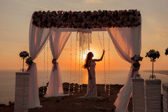 Sunset. bride silhouette. Wedding ceremony arch with flower arra Stock Photo