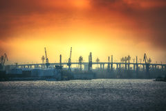 Sunset and bridge with cranes royalty free stock photography