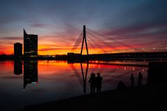 Sunset at the bridge on the Daugava River in Riga. Sunset at the cable bridge on the Daugava River in Riga is watched by people silhouettes royalty free stock photography