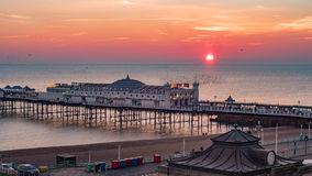 Sunset on Brighton pier with a flock of birds stock photography