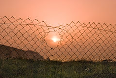 Sunset through a broken wire fence. Royalty Free Stock Photos
