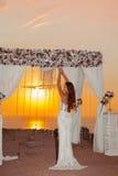 Sunset. Brunette bride portrait. Wedding ceremony arch with flow Stock Images