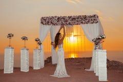 Sunset. Brunette bride Wedding ceremony arch with flower arrange Stock Images