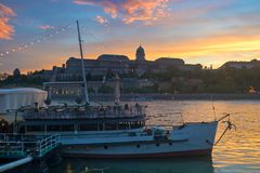 Sunset in Budapest, King`s Palace outline. King`s Palace view over Danube river with a boat and sky reflected in the river Royalty Free Stock Photography