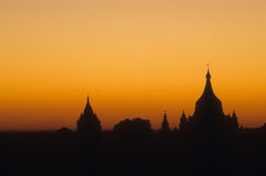 Sunset with Buddhist temples on horizon, Royalty Free Stock Images